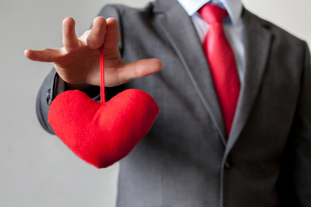controling: Businessman winning and controling customers heart concept.