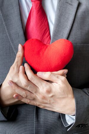 man business oriented: Businessman showing compassion holding red heart onto his chest in his suit - crm, service mind business concept