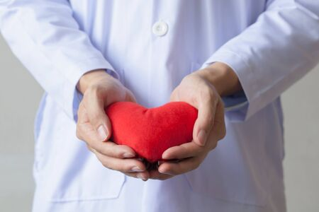 life giving birth: Doctor giving a heart shape object in white isolated background.