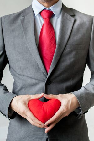 man business oriented: Businessman showing compassion holding red heart in his suit - crm, service mind business concept.