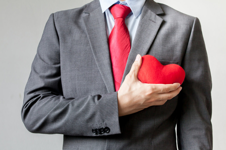 man business oriented: Businessman showing compassion holding red heart onto his chest in his suit - crm, service mind business concept.