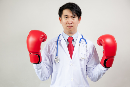 Hospital care: Asian Doctor wearing boxing gloves in white background