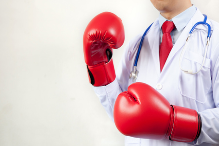 Hospital care: Doctor wearing boxing gloves in white background