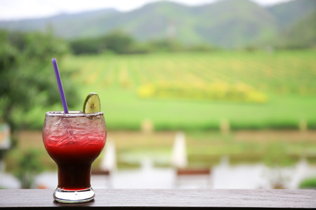 Glass of iced cocktail in winery vineyard hill in background. Stock Photo
