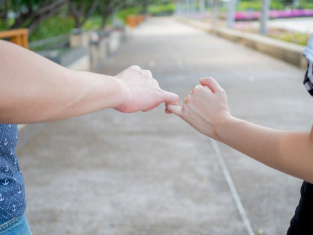 promised: Man and woman in relationship crossing pinky finger as promised