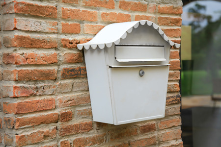 Vintage white mail box hanging on red brick wall (selective focus).