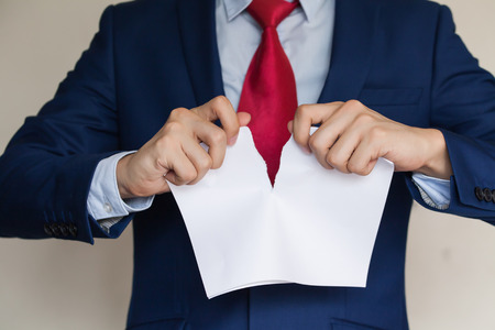 tearing: Businessman tearing blank paper apart on white background