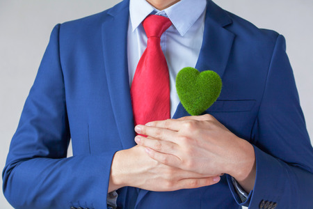 environmental responsibility: Businessman in suit holding a green heart shape - white background - indicates eco-friendly , social and environmental responsibility business concept Stock Photo