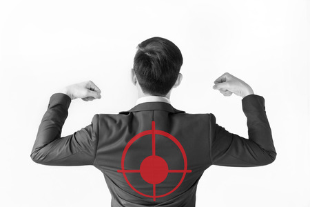 Strong businessman flexing his muscle with red target on his back - indicates accurate marketing, targeting advertising Stock Photo