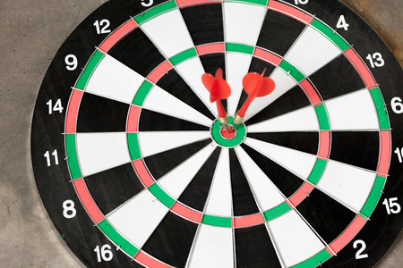 accurately: Darts accurately and perfectly hit the winning red spot on board - indicates right targeting, marketing, focus concept.