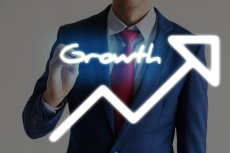 upward: Businessman drawing GROWTH and upward graph arrows forward