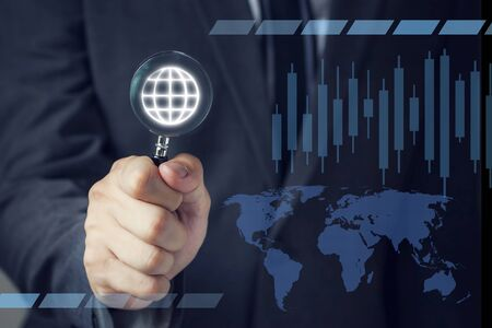 virtual world: Businessman in suit looking for virtual world using a small magnifier. Stock Photo