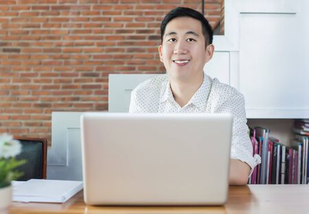 selectively: Handsome Asian businessman with computer in cafe (selectively focus on face). Stock Photo
