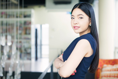 Asian woman having arms folded on office background (Focus on eyes)