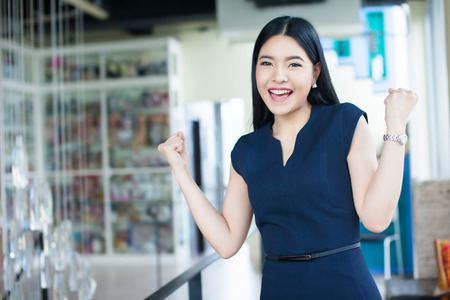 Excited Asian woman raising her arms showing happiness - success and business concept.
