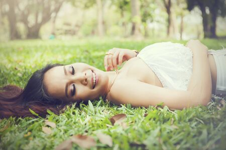 woman laying down: Young happy and smiling woman laying down on green grass (Vintage tone) Stock Photo