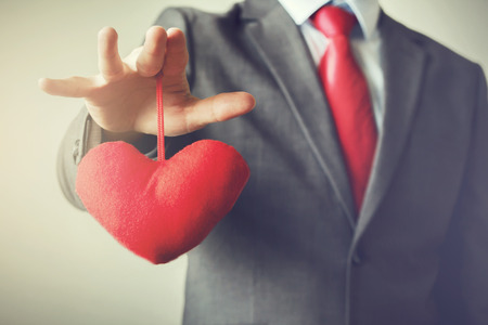 controling: Businessman winning and controling customers heart concept in Vintage tone Stock Photo