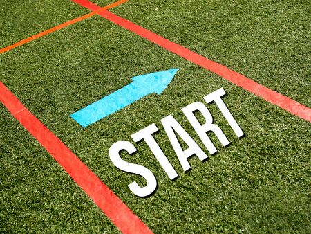 challenges ahead: Start written on the green grass of the race Stock Photo