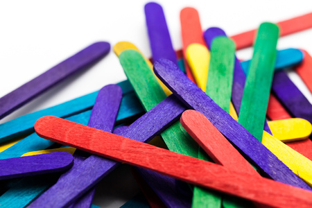 wood craft: Colorful popsicle sticks over white background (Shallow depth of field).