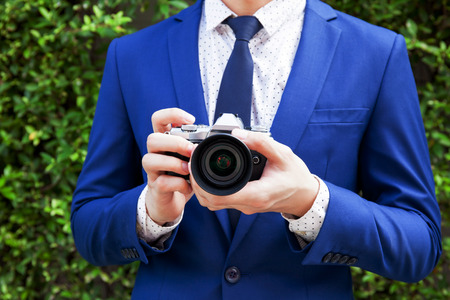 (Close-up) Young professional photographer taking photos in green bushes outdoor background Stock Photo
