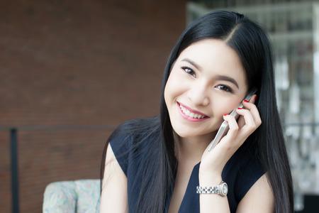 La mujer asiática hermosa que habla en el teléfono en la oficina. Foto de archivo - 60672801