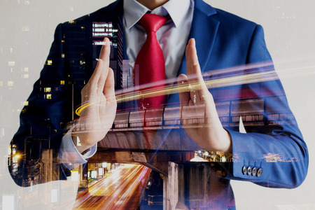 Double exposure of businessman in protecting position with night cityscape.