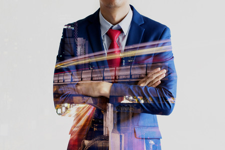 Double exposure of confident businessman dissolved with long shutter speed night cityscape