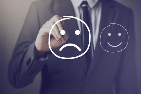 elección del cliente para escribir sobre la cara infeliz cara feliz en la pantalla virtual Foto de archivo