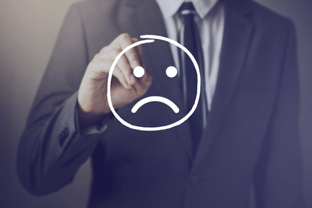 Businessman writing unhappy face on virtual screen.