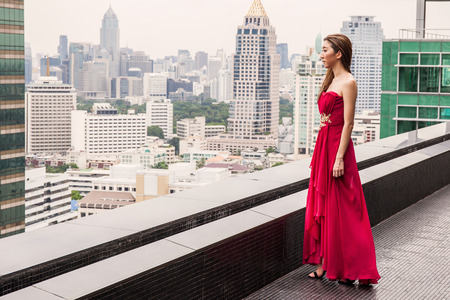 snob: Asian female model in red evening dress standing on the rooftop of high rise building