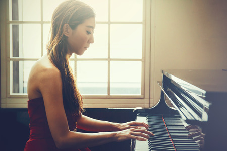 Asian woman playing piano in window background with light coming in (Vintage tone) Banco de Imagens