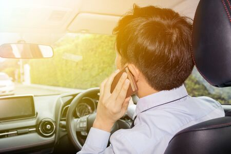 careless: Asian businessman talking on phone while driving - careless lifestyle and risk concept