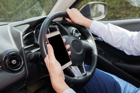 distraction: Businessman checking phone while careless driving - distraction and bad habit driving concept - with clipping mask on screen