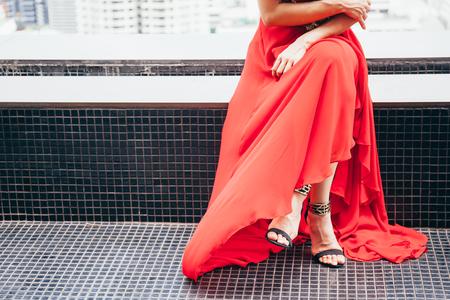 Donna alla moda seduta gambe incrociate in abito rosso lungo in scena urbana dietro