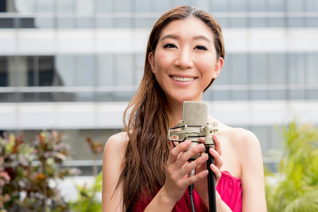 Asian vocalist happily smiling and singing with mic on rooftop of the building