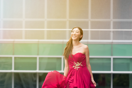 red evening: Happy and smiling cute Asian woman walking in red evening dress.