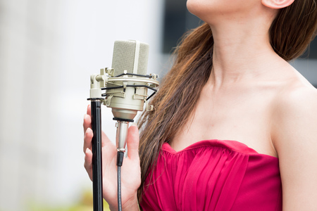 performace: Close-up of woman singing and performing with mic in outdoor scene.