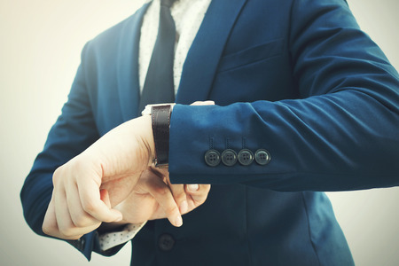Fashionable businessman in elegant blue suit looking at luxury watch in hurry. Stock Photo