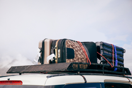 over packed: Luggages and Bags arranged on the car roof ready for a trip in sky background
