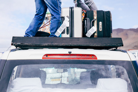 duffle: Luggages and Bags arranged on the car roof ready for a trip in sky background