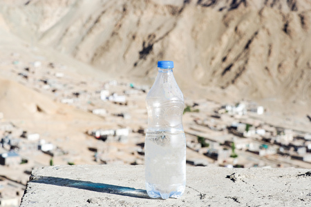 dehydration: Bottle of water in desert land - hydration and dehydration concept.