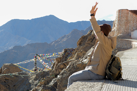Male traveler raising hands as he successfully climbed up to the top of high mountain.