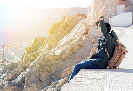 extremely: Extremely happy and joyful male traveler sitting and raising hands up in mountain area. Stock Photo
