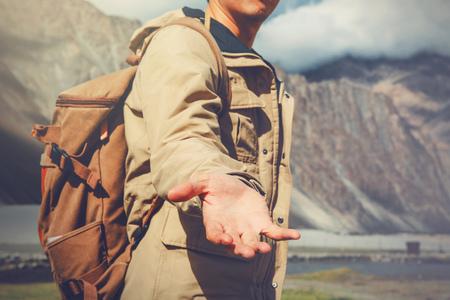 Jonge reizen man een helpende hand in openlucht berglandschap.