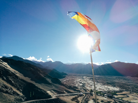One single Buddhist prayer flag in six colors fluttering in mountain region against the sunlight. - The colorful flags can represent Tibetan culture and Buddhist religion symbol very well. Stock Photo