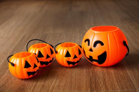 jack'o'lantern: Group of happy and smiling jack-o-Lantern pumpkin buckets on wooden background. Stock Photo