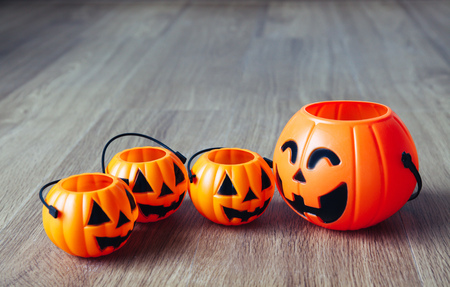 Group of happy and smiling jack-o-Lantern pumpkin buckets on wooden background. Stock Photo