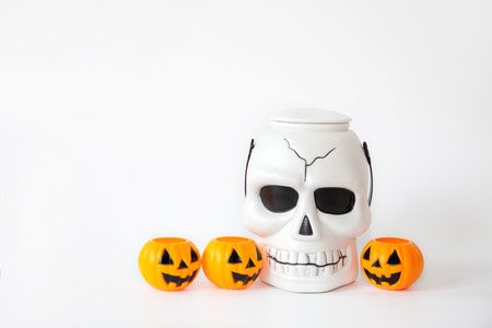 Skull and orange jack-o-lantern pumpkin buckets in white isolated background.