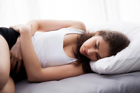 Junge schöne kaukasischen Frau auf dem Bett, traurig zu sein, deprimiert, Magenschmerzen hat, Lebensmittelvergiftung, die, Krämpfe Übelkeit