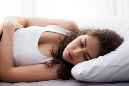 cramps: Young beautiful Caucasian woman on bed being sad, depressed, having stomach pain, having food poisoning, cramps sickness Stock Photo